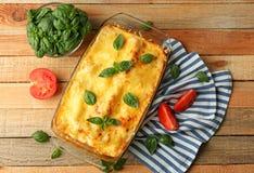 Traditionele lasagna's in de schotel en de tomaten van het glasbaksel royalty-vrije stock foto