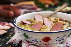 Traditionele Nederlandse erwtensoep en ingrediënten op een rustieke lijst Stock Fotografie