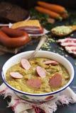 Traditionele Nederlandse erwtensoep en ingrediënten op een rustieke lijst Stock Afbeelding