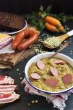 Traditionele Nederlandse erwtensoep en ingrediënten op een rustieke lijst Stock Foto
