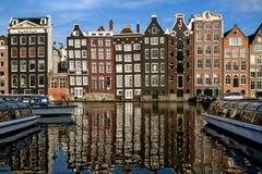 Traditionele Nederlandse middeleeuwse die gebouwen binnen langs de kanaalkant, in water wordt weerspiegeld Zonnige dag Amsterdam, Stock Fotografie