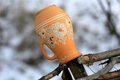 Traditionele Oekraïense kleikruik op een houten omheining in dorp stock afbeeldingen
