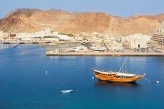Traditionele Omani boot Dhow in de haven van Mutrah in Muscateldruif en op de achtergrond de vissenmarkt en Corniche stock afbeelding
