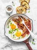 Traditionele ontbijt of snack - gebraden eieren, bacon, geroosterd brood op lichte achtergrond, hoogste mening royalty-vrije stock foto's
