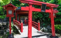 Traditionele rode Brug, Lantaarn en Torii aan het Japanse die Heiligdom van Jigoku Meguri Shinto door een groen landschap wordt o royalty-vrije stock fotografie