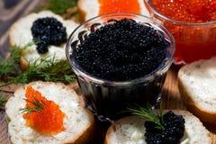 traditionele rode en zwarte kaviaar en sandwiches op houten raad Stock Foto