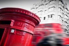 Traditionele rode postbrievenbus en rode bus in motie in Londen, het UK stock afbeelding