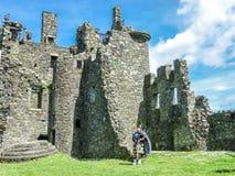 Traditionele Schotse bagpiper bij ruïnes van Kilchurn-kasteel Royalty-vrije Stock Afbeelding