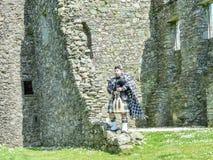 Traditionele Schotse bagpiper bij ruïnes van Kilchurn-kasteel Stock Foto