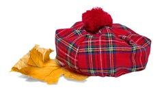 Traditionele Schotse Rode Geruit Schots wollen stofbonnet en Droog Esdoornblad stock foto's