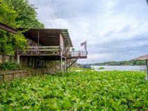 Traditionele Thaise huisstijl dichtbij de rivier in Thailand met de mooie blauwe hemel van de waterhyacint Stock Afbeelding