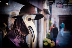 Traditionele Venetiaanse ledenpop in Plaag artsenkostuum, masker en hoed dichtbij winkelvenster in de straat van Venetië, Italië  Stock Foto's