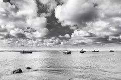 Traditionele vissersboten in haven met oceaan en wolken i Stock Foto