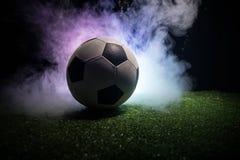 Traditionele voetbalbal op voetbalgebied Sluit omhoog mening van voetbalbal (voetbal) op groen gras met donkere gestemde mistige  royalty-vrije stock fotografie