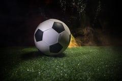 Traditionele voetbalbal op voetbalgebied Sluit omhoog mening van voetbalbal (voetbal) op groen gras met donkere gestemde mistige  Stock Foto's