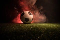Traditionele voetbalbal op voetbalgebied Sluit omhoog mening van voetbalbal (voetbal) op groen gras met donkere gestemde mistige  royalty-vrije stock afbeeldingen