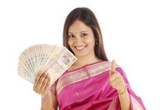 Traditionele vrouw die Indische munt houdt stock foto
