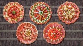 Traditionele welkome versierde voorgerecht smakelijke die schotels op de doorweven donkere mat van het pakpapierperkament worden  Stock Fotografie