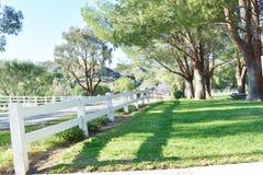 Traditionele witte houten omheiningsgrenzen een mooi park als het plaatsen stock foto's