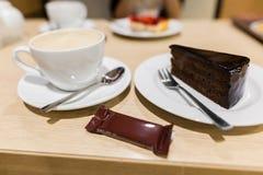 Traditionell österrikisk sachertorte på plattan på träbakgrund kopp för cakechokladkaffe Arkivfoto