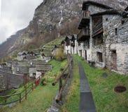 Traditionell alpin by med många små trä- och stenhus och en bergvattenfallbakgrund fotografering för bildbyråer