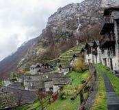 Traditionell alpin by med många små trä- och stenhus och en bergvattenfallbakgrund royaltyfri bild