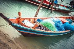 Traditionell asiatisk fiskebåt med fisknät som förtöjas till stranden royaltyfri bild