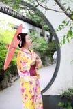 Traditionell asiatisk japansk kvinna i en trädgårds- håll ett rött paraply Arkivbild