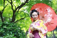 Traditionell asiatisk japansk kvinna i en trädgårds- håll ett rött paraply Arkivbilder