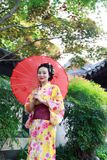 Traditionell asiatisk japansk kvinna i en trädgårds- håll ett rött paraply Arkivfoton
