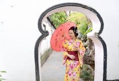 Traditionell asiatisk japansk kvinna i en trädgårds- håll ett rött paraply Fotografering för Bildbyråer