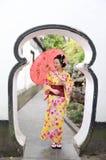 Traditionell asiatisk japansk kvinna i en trädgårds- håll ett rött paraply Royaltyfria Bilder