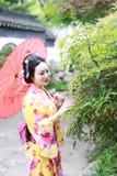 Traditionell asiatisk japansk kvinnabrudhåll ett rött paraply som ler i en trädgård Arkivbilder