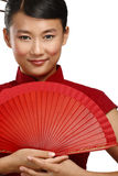 Traditionell asiatisk kvinna som rymmer en röd härlig fan royaltyfri fotografi