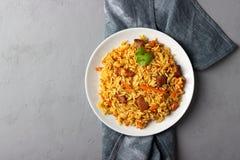Traditionell asiatisk maträtt - pilaff från från ris, grönsaker och kött i en platta royaltyfri foto