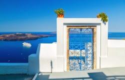 Traditionell blå dörr på den Santorini ön, Grekland, med sikt över det vulkaniska caldera- och kryssningskeppet Royaltyfri Fotografi