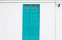 Traditionell blå dörr som är trä av ett gammalt på den vita väggen royaltyfria bilder
