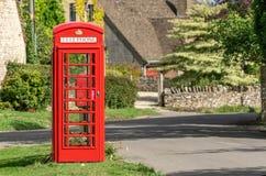 Traditionell brittisk röd telefonask i en Cotswold by royaltyfri fotografi