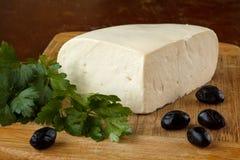 Traditionell bulgarian ny keso från ko mjölkar på en skärbräda som dekoreras med oliv och persilja Arkivbilder