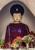 Traditionell burmesebuddha staty med den röda ämbetsdräkten och gloria Royaltyfri Bild