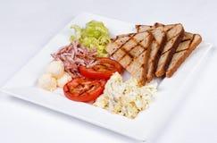 Traditionell engelsk frukost med förvanskade ägg Arkivfoton