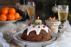 Traditionell engelsk jul ångad pudding med vinterbär, torkade frukter, mutter i den festliga inställningen med Xmas-trädet, brinn royaltyfria bilder