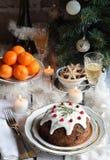 Traditionell engelsk jul ångad pudding med vinterbär, torkade frukter, mutter i den festliga inställningen med Xmas-trädet, brinn fotografering för bildbyråer