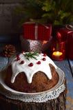 Traditionell engelsk jul ångad pudding med vinterbär, torkade frukter, muttern i festlig inställning med Xmas-trädet och bränning Fotografering för Bildbyråer