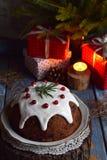 Traditionell engelsk jul ångad pudding med vinterbär, torkade frukter, muttern i festlig inställning med Xmas-trädet och bränning royaltyfri foto