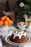 Traditionell engelsk jul ångad pudding med vinterbär, torkade frukter, muttern i festlig inställning med Xmas-trädet och bränning royaltyfri bild
