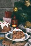 Traditionell engelsk jul ångad pudding med vinterbär, torkade frukter, muttern i festlig inställning med Xmas-trädet och bränning royaltyfria foton