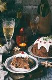 Traditionell engelsk jul ångad pudding med vinterbär, torkade frukter, muttern i festlig inställning med Xmas-trädet och bränning arkivfoton