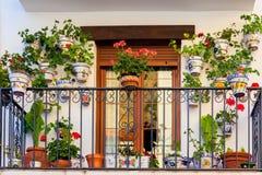 Traditionell europeisk balkong med blommor och blomkrukor Arkivbilder