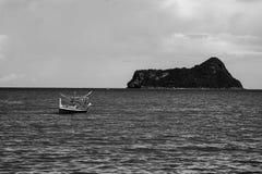 Traditionell fiskebåt som bara lägger på havet med ön i bakgrund, selektiv fokus, svartvit färgbildstil Royaltyfri Bild